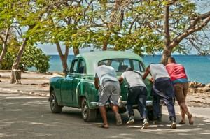 Ein Oldtimer wird am Playa La Boca Kuba angeschoben